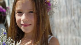 Cute red-haired girl with flower`s crown on the head smiling at camera. Full HD stock video