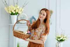 Cute red-haired girl holding a basket of flowers and smiling, Ea Stock Image