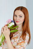 Cute red-haired girl holding flowers and smiling, close-up Stock Photo
