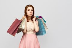 Cute red-haired girl with inflated lips wants to buy a dress and asks the boyfriend to give her more money for shopping royalty free stock photography
