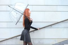 Cute red-haired girl with an umbrella. Young cute red-haired girl with an umbrella Stock Photography