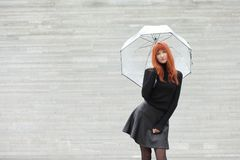 Cute red-haired girl with an umbrella. Young cute red-haired girl with an umbrella Stock Image