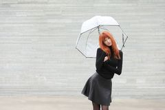 Cute red-haired girl with an umbrella. Young cute red-haired girl with an umbrella Royalty Free Stock Image