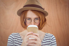 Cute red haired hipster with glasses holding disposable cup. On wooden background Stock Images