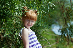 Cute red-haired little girl posing near tree Stock Photos