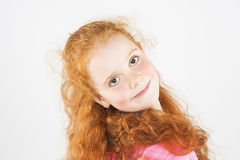Cute Red-haired Little Smiling Girl. Standing Against White Back Royalty Free Stock Image