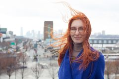 Cute red-haired woman in a blue coat and glasses standing on the background of the big city, her hair fluttering in the. Wind, portrait Royalty Free Stock Photos