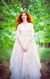 Cute red-haired woman wearing white dress in a garden Stock Images