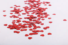 Cute red scattered sequin hearts on a white background. Perfect for weddings and valentines Royalty Free Stock Photography