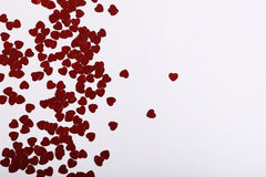 Cute red scattered sequin hearts on a white background Stock Photos