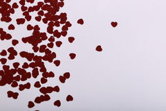 Cute red scattered sequin hearts on a white background Stock Photography