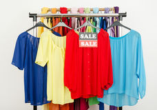 Cute red, yellow, blue blouses displayed on hangers with the sale sign. Stock Photo