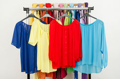 Cute red, yellow, blue blouses displayed on a rack. Stock Images