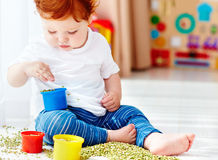Cute Redhead Baby Boy Developing His Fine Motility Skills By Playing With Green Peas At Home Royalty Free Stock Photo