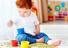 Cute redhead baby boy developing his fine motility skills by playing with green peas at home Royalty Free Stock Photography