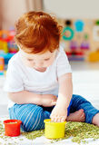 Cute redhead baby boy developing his fine motility skills by playing with green peas at home Royalty Free Stock Images