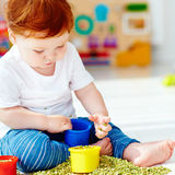 Cute redhead baby boy developing his fine motility skills by playing with green peas at home Stock Photography
