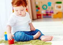 Cute redhead baby boy developing his fine motility skills by playing with green peas at home Stock Photo