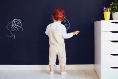 Cute redhead baby boy drawing on the chalk wall at home royalty free stock photos