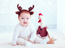 Cute redhead baby with rooster toy at home Royalty Free Stock Images
