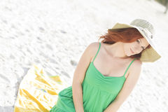 Cute redhead at the beach. A beautiful woman wearing a hat at the beach Royalty Free Stock Images
