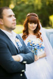 Cute redhead bride holding bouquet and looking at groom Royalty Free Stock Photo