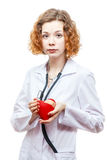 Cute redhead doctor in lab coat with heart. Isolated on white background Royalty Free Stock Image