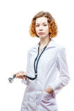 Cute redhead doctor in lab coat with stethoscope. Isolated on white background Stock Photo