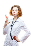 Cute redhead doctor in lab coat with syringe. Isolated on white background Stock Photo