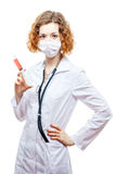 Cute redhead doctor in lab coat with syringe in mask. Isolated on white background Royalty Free Stock Photography
