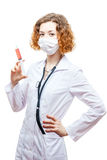 Cute redhead doctor in lab coat with syringe in mask. Isolated on white background Royalty Free Stock Photo
