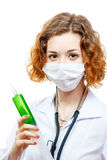 Cute redhead doctor in lab coat with syringe in mask. Isolated on white background Royalty Free Stock Image