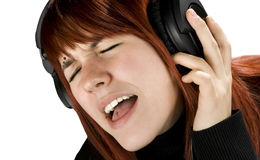 Cute redhead enjoying music. Cute redhead girl enjoying and singing music on her headphones. Studio shot royalty free stock photography