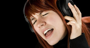 Cute redhead enjoying music. Cute redhead girl enjoying and singing music on her headphones Royalty Free Stock Photos