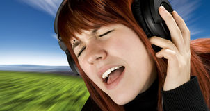 Cute redhead enjoying music. Cute redhead girl enjoying and singing music on her headphones Stock Image