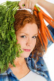 Cute redhead with fresh carrots Stock Photography
