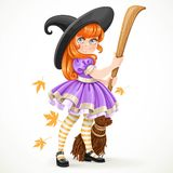 Cute redhead girl dressed as a witch holding a broom for flying Stock Photography
