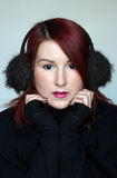 Cute redhead girl in the fur ear muffs Royalty Free Stock Photos