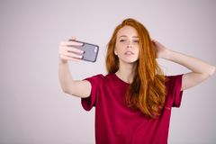 Redhead girl takes a selfie. She has long red hair. wears marsala t-shirt royalty free stock photo