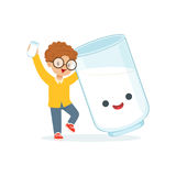 Cute redhead little boy and funny milk glass with smiling human face playing and having fun, healthy childrens food Royalty Free Stock Images