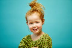 Cute redhead little girl isolated on blue background. stock photos