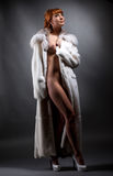 Cute redhead nude model advertises luxury fur coat Stock Photos