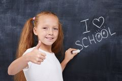 Cute redhead schoolgirl showing thumbs up and Stock Images