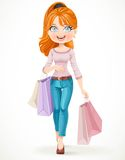Cute redhead shopaholic girl goes with paper bags in hands Stock Photo