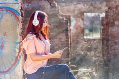 Cute redhead teenage lady with digital tablet listening music on headphones and sittings on ruins wall bricks of house in sunset stock photo