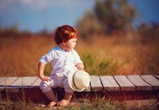 Funny redhead toddler baby boy sitting on wooden path at summer field Stock Photo