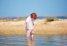 Cute redhead toddler baby boy soaks clothes in shallow water at morning lake. Funny redhead toddler baby boy soaks clothes in shallow water at morning lake Stock Image