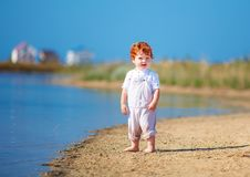 Cute redhead toddler baby boy walking at lake coast in the summer morning. Cute happy redhead toddler baby boy walking at lake coast in the summer morning royalty free stock images