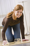 Cute Redhead Woman Cleaning Up a Spill. Attractive young redhead woman cleaning up a water spill in her home. Vertically framed photo royalty free stock photography