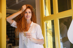 Cute redhead woman with long hair holding cup of coffee. Portrait of a cute redhead woman with long hair holding cup of coffee while standing near cafe Royalty Free Stock Images
